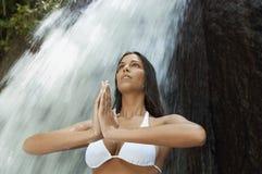 妇女用被扣紧的手执行瑜伽反对瀑布 免版税库存照片