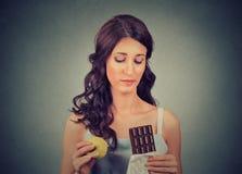 妇女用设法的巧克力和的苹果做出一个健康选择控制她的体重 在背景空白弓概念节食的显示评定编号附近自己的缩放比例磁带文本附加的空白视窗包裹了您 免版税图库摄影