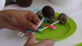 妇女用辫子蛋糕流行音乐弓在板材装饰并且投入它 用驱散不同颜色装饰的糖果 股票视频