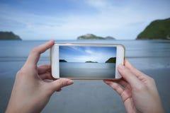 妇女用途巧妙的电话在Prachuapkhirikhan,泰国拍海的照片 免版税库存照片