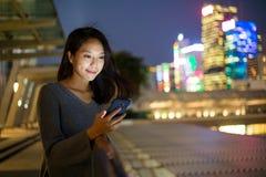 妇女用途手机在晚上 库存图片