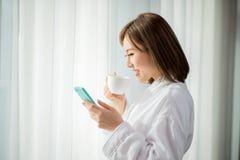妇女用途智能手机在早晨 库存图片