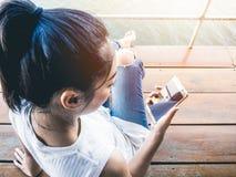 妇女用途智能手机她的假日 免版税库存图片