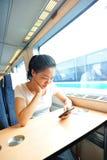 妇女用途火车智能手机内部  免版税库存照片
