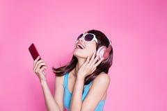 妇女用途电话听音乐 免版税库存照片