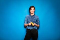妇女用香蕉在手上在蓝色背景 免版税图库摄影