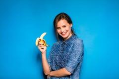 妇女用香蕉在手上在蓝色背景 免版税库存图片
