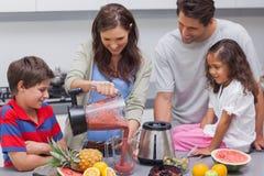妇女用从搅拌器的家庭倾吐的果子 免版税库存照片