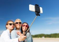 妇女用selfie棍子和智能手机在海滩 免版税库存照片