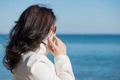 妇女由手机讲话在海边 免版税库存照片