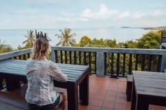 妇女由桌坐咖啡馆空的大阳台  免版税库存照片