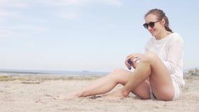 妇女由海坐 她抹上她的腿与晒斑奶油 影视素材