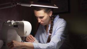妇女由灯的光缝合在一台缝纫机的衣裳 时尚,创作和剪裁 影视素材