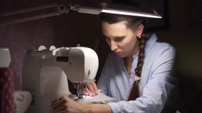 妇女由灯的光缝合在一台缝纫机的衣裳 时尚,创作和剪裁 股票录像