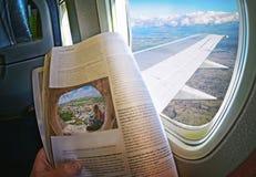 妇女由窗口坐有杂志的一架飞机在手上 免版税库存照片