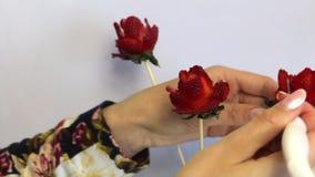 妇女由草莓做一朵玫瑰 草莓在棍子穿戴,妇女切开有刀子的瓣 它改正 股票视频