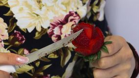 妇女由草莓做一朵玫瑰 草莓在棍子穿戴,妇女切开有刀子的瓣 它改正 影视素材