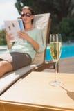 妇女由水池的阅读书用在前景的香槟 库存照片