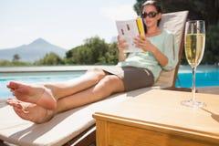 妇女由水池的阅读书用在前景的香槟 库存图片