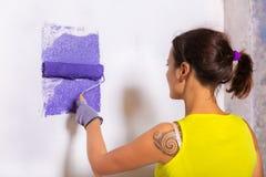 妇女由紫色路辗绘墙壁 免版税库存照片