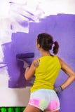 妇女由紫色路辗绘墙壁 库存图片