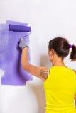 妇女由紫色路辗绘墙壁 图库摄影