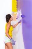 妇女由紫色路辗绘墙壁 免版税图库摄影