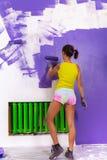妇女由紫色路辗绘墙壁 库存照片