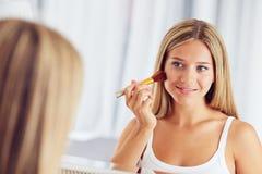 妇女申请用一把大刷子和看组成在镜子 库存照片