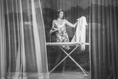 妇女电烙的衣裳在家 库存照片