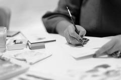 妇女画在纸的一支色的铅笔 图库摄影