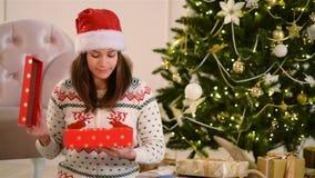 妇女画象圣诞老人帽子的打开当前箱子 圣诞树在背景 概念新年好 影视素材