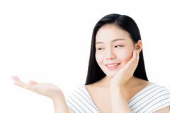 妇女画象是微笑的皮肤秀丽和健康和举她的手,好象拿着在她的手上的一个产品 免版税库存照片