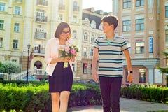 妇女画象有花和十几岁的男孩花束的城市背景的 儿子祝贺了他的母亲 免版税库存图片