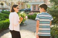 妇女画象有花和十几岁的男孩花束的城市背景的 儿子祝贺了他的母亲 库存照片