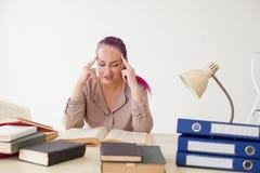 妇女疲倦了在办公室和阅读书的工作 库存图片