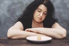 妇女疲倦于热衷甜点的饮食制约 库存图片