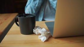 妇女病,坐在膝上型计算机的一个咖啡馆,抹她的鼻子与手帕 影视素材
