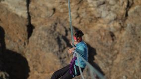妇女登山人被送横跨峡谷的绳索 股票录像