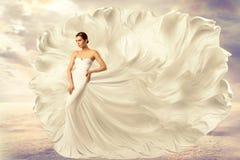 妇女白色礼服,在长的丝绸挥动的褂子,在风的飞行的振翼的织品的时装模特儿 免版税库存照片
