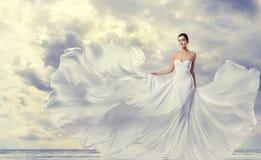 妇女白色礼服,在长的丝绸振翼的褂子,在风的挥动的飞行的布料的时装模特儿 免版税图库摄影