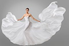 妇女白色礼服,在长的丝绸新娘褂子的婚姻的时装模特儿 免版税图库摄影