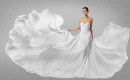 妇女白色礼服,在长的丝绸褂子,挥动的布料的时装模特儿 库存图片