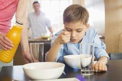 妇女的中央部位有汁液瓶支持的儿子的吃与人的早餐在背景 免版税图库摄影