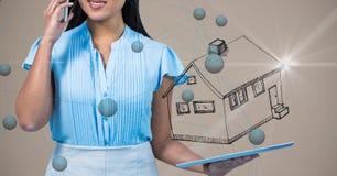 妇女的中央部位谈话在手机,当拿着有房子标志和conne的时数字式片剂 免版税库存照片