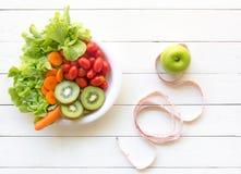 妇女的健康生活方式节食与测量的磁带,在白色木的菜新鲜,绿色苹果 免版税库存图片