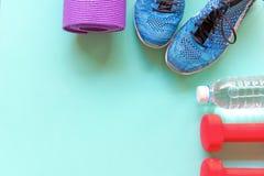 妇女的健康生活方式节食用运动器材、运动鞋和新鲜的瓶在木的水 免版税库存图片