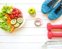妇女的健康生活方式节食用运动器材、运动鞋、测量的磁带、菜新鲜,绿色苹果和瓶水 免版税库存照片
