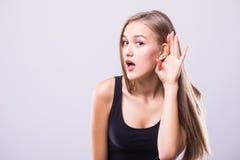 妇女的关闭在耳朵附近在灰色墙壁背景握她的手并且听小心地隔绝 人的情感肢体语言脸面护理 免版税图库摄影