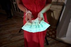 妇女的关闭红色礼服的拿着金钱 库存照片